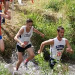 Kristoffer Larsen Running Through Creek wearing his Norwegian Flag Socks